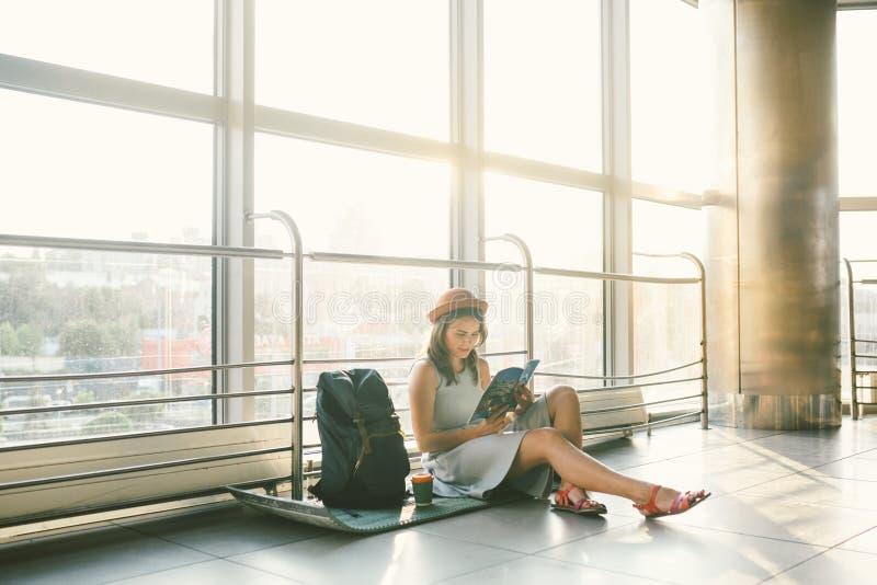 Vänta, försenad transport i terminalen av flygplatsen eller drevstation Den unga caucasian kvinnan i klänning och hatt sitter på  royaltyfri fotografi