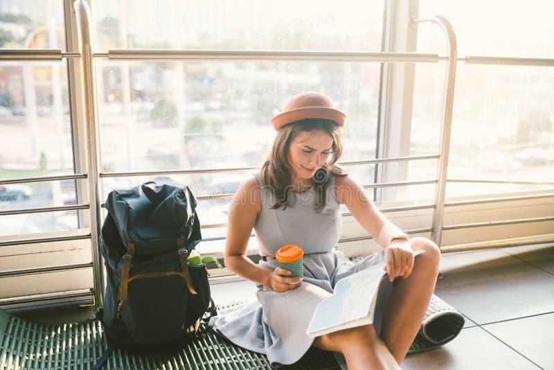 Vänta, försenad transport i terminalen av flygplatsen eller drevstation Den unga caucasian kvinnan i klänning och hatt sitter på  royaltyfri foto