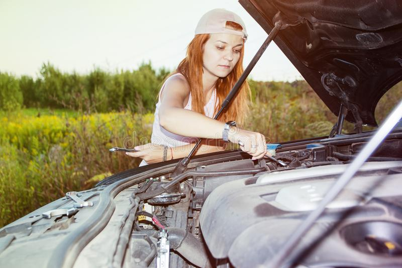 Vänta på vägrenhjälp Stående av ett anseende för ung kvinna bredvid hennes bil som försöker att fixa motorn fotografering för bildbyråer