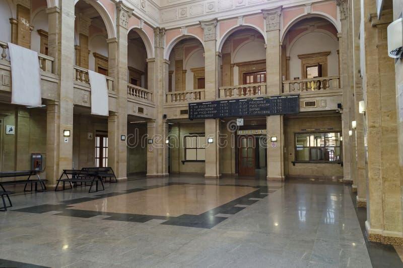 Vänta-rummet med den tomma affischtavlaannonseringen i den gamla järnvägsstationen royaltyfri foto
