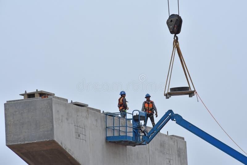 Väntan för två brobyggnadsarbetare på brodelar royaltyfria foton