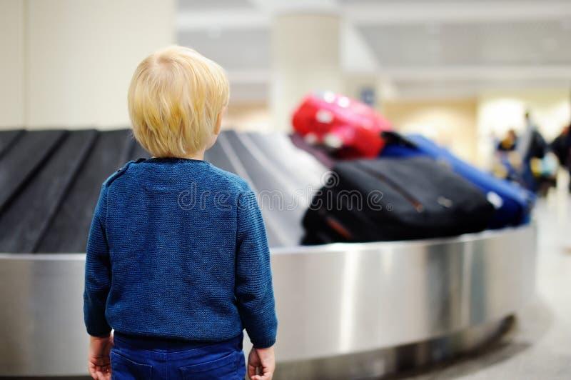 Väntande bagage för trött barn på flygplatsen royaltyfri bild