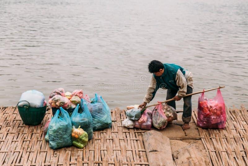 Väntande fartyg för man för rörande artiklar i floden på Luang Prabang, Laos arkivbild