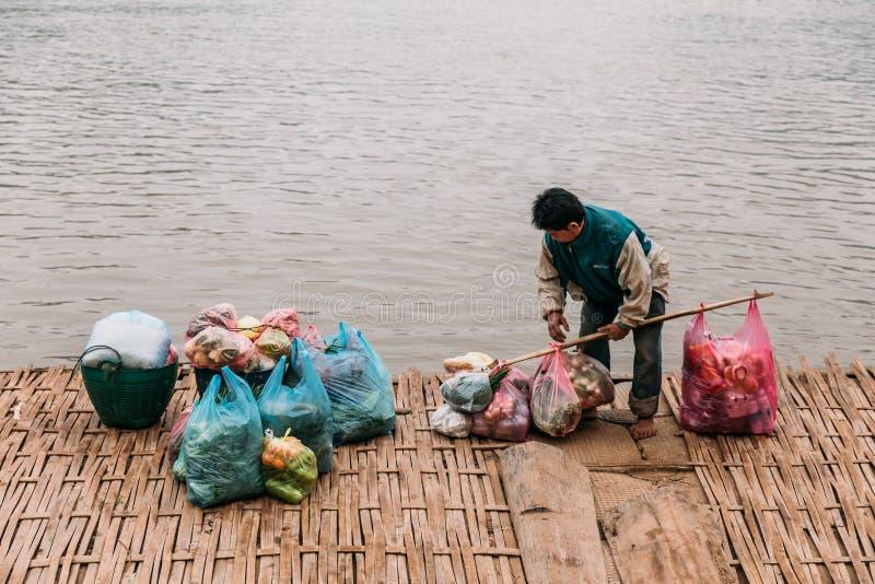 Väntande fartyg för man för rörande artiklar i floden på Luang Prabang, Laos arkivbilder