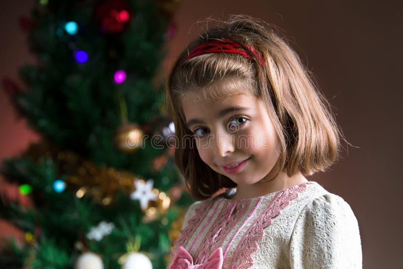 Väntande julgåva för lycklig ung flicka under trädet hemma arkivfoto