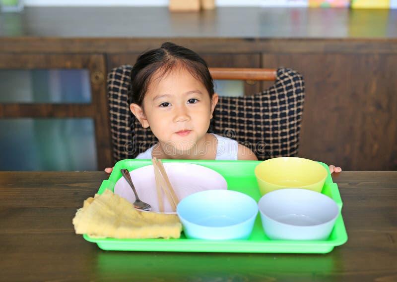 Väntande mat för liten asiatisk flicka på tabellen med många tom bunke arkivbilder