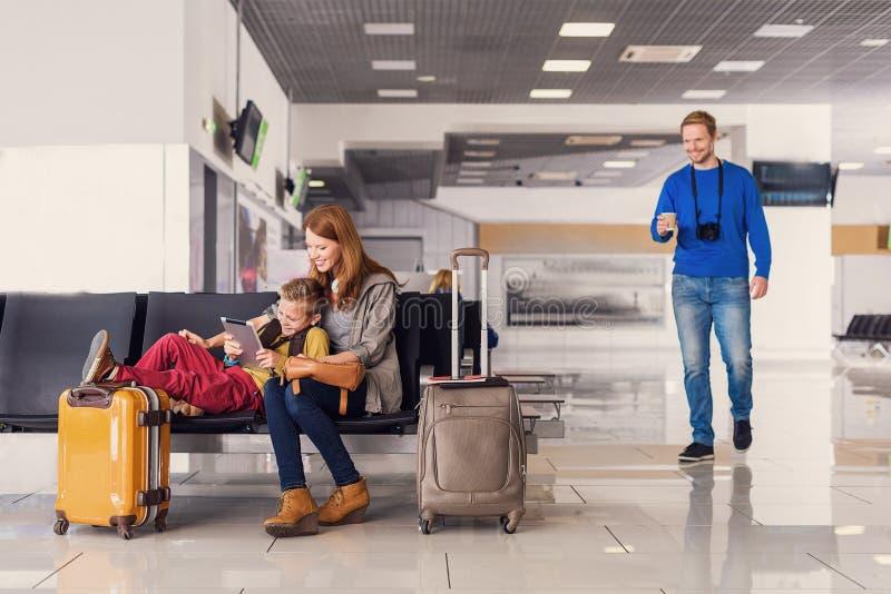 Väntande på avvikelse för familj på flygplatsen arkivbilder