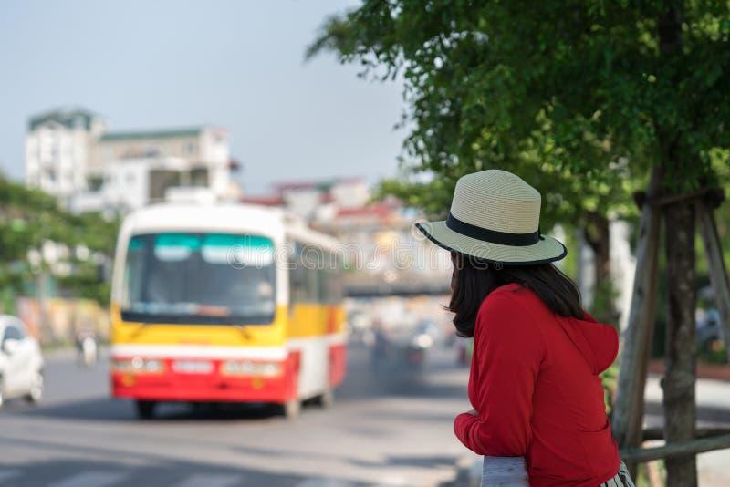 Väntande på buss för ung flicka på bussstationen closeup arkivfoto
