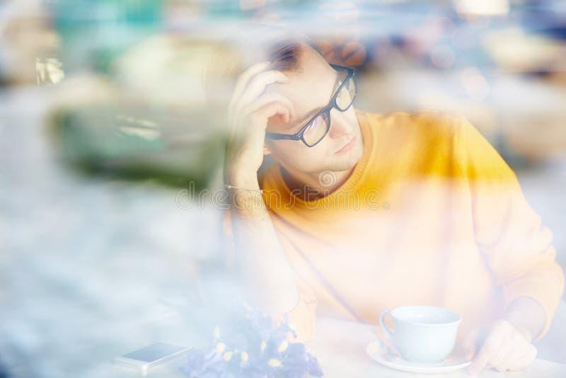Väntande på datum för eftertänksam man i kafé fotografering för bildbyråer