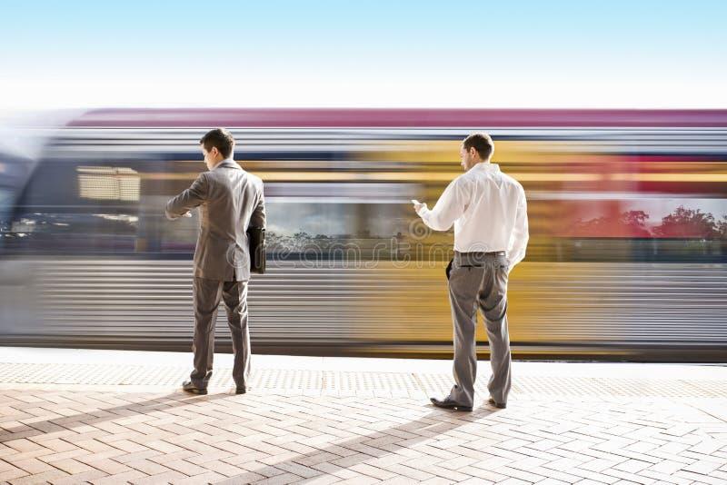Väntande på drev för två kontorspersoner på stationen royaltyfri fotografi
