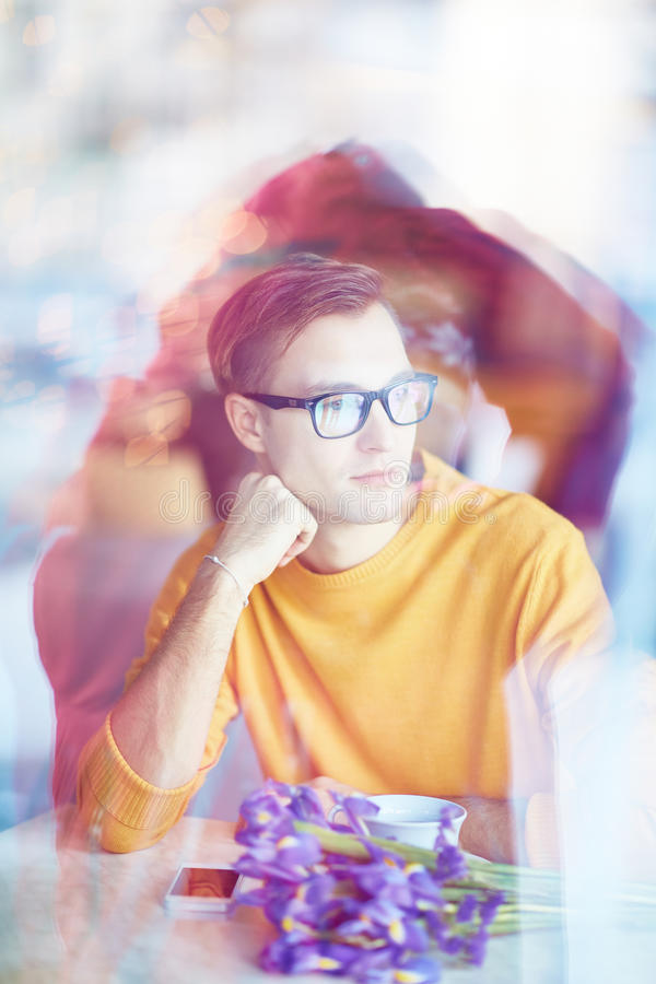 Väntande på första datum för ung man i kafé arkivbild