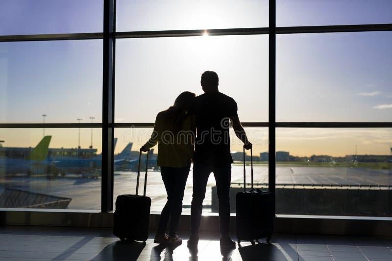 Väntande på flyg för par i flygplats royaltyfri bild