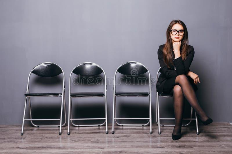 Väntande på jobbintervju för ung kvinna i korridoren arkivfoto