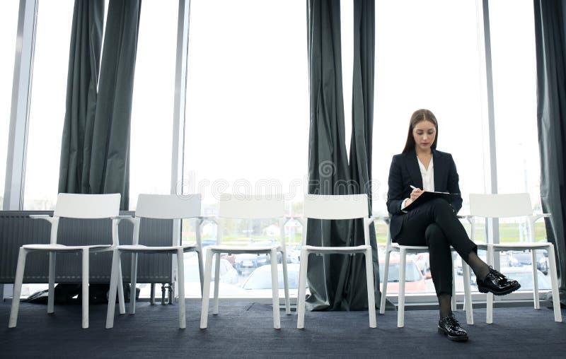 Väntande på jobbintervju för ung kvinna inomhus royaltyfri fotografi