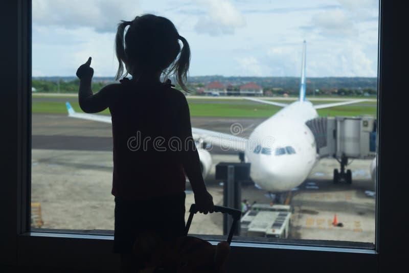 Väntande på logi för litet barn till flyget i flygplatsterminal arkivbild