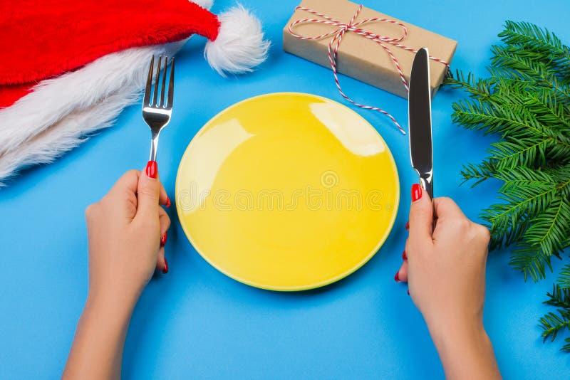 Väntande på mål för hungrig kvinna tom gul platta på en blå bakgrund med julfilialer, den santa hatten och gåvaasken Perspectiv royaltyfria foton