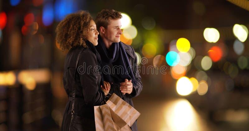 Väntande på ritt för attraktiva par utomhus med shoppingpåsar royaltyfri bild