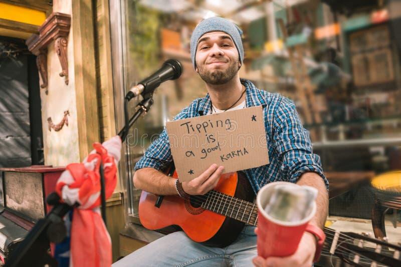 Väntande på spetsar för nöjd manlig musiker efter lek arkivbild