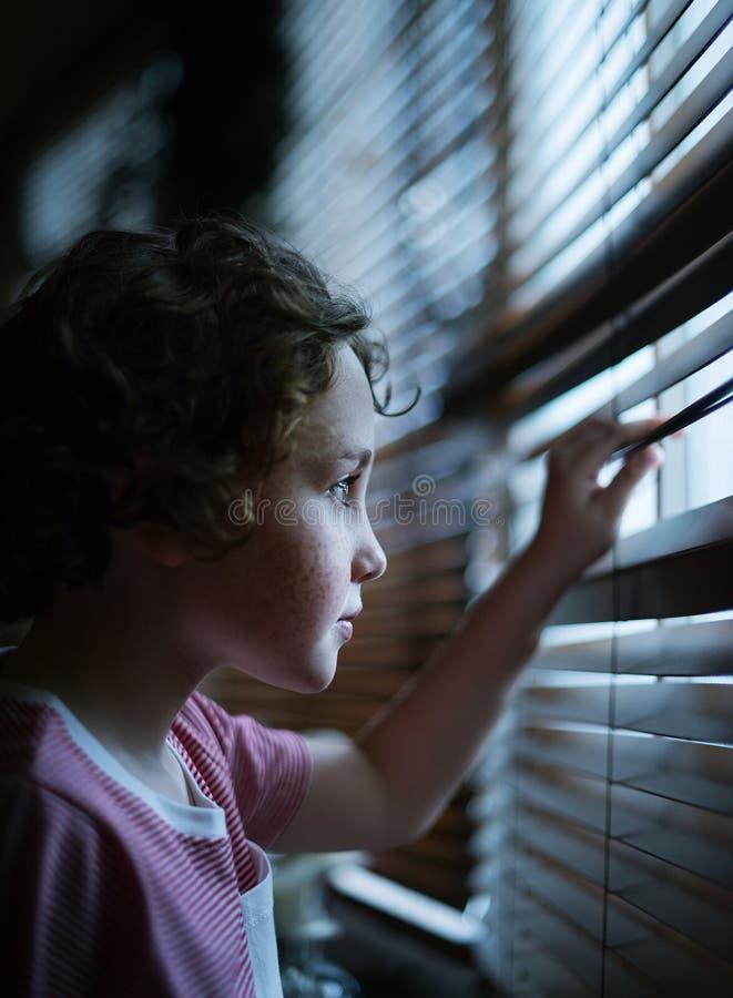 Väntande stirra för ung Caucasian pojke på ett fönster royaltyfri foto
