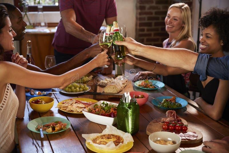 Värd och vänner som gör upp ett rostat bröd på ett matställeparti, slut arkivfoton