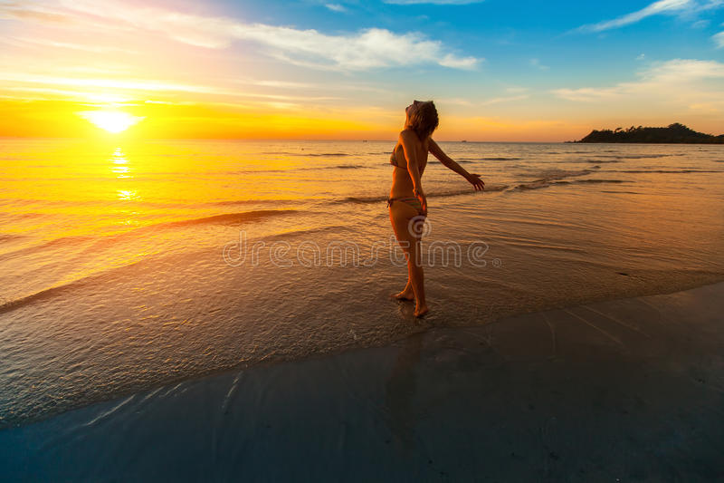 Värde för ung kvinna in mot den härliga solnedgången royaltyfria foton