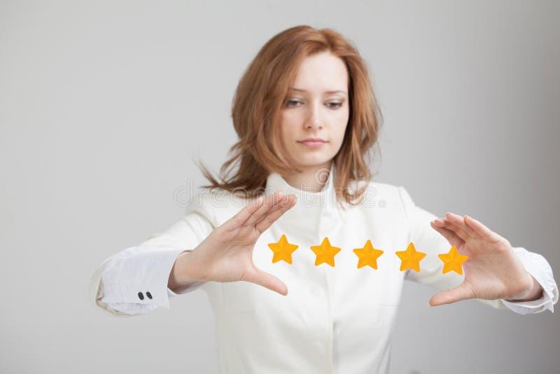 Värdering eller rang för fem stjärna som jämför begrepp Kvinnan bedömer service, hotellet, restaurang arkivfoto
