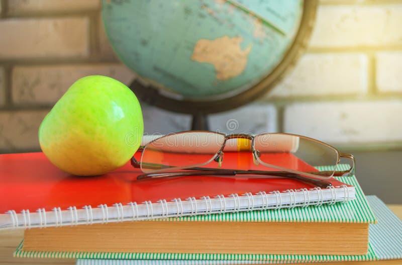 Värld teacher' s-dag på skola Stilleben med böcker, jordklot, Apple, exponeringsglas, solljus arkivfoton