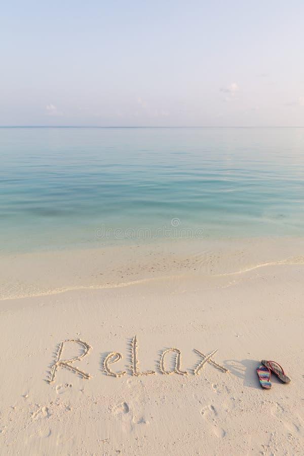 Världen KOPPLAR AV skriftligt på sand tidigt på morgonen på den cristal rena stranden av Maldiverna arkivbilder