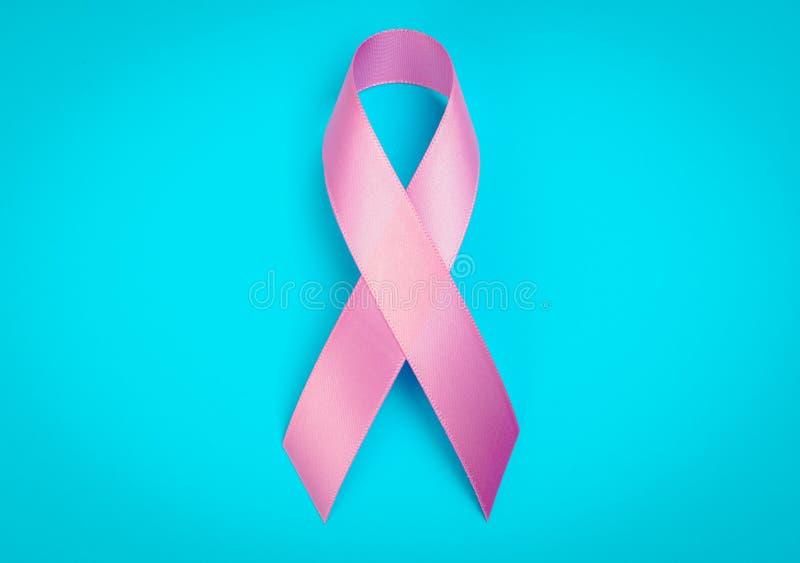Världscancerdag: Bröstcancermedvetenhetband på blåa Backgr royaltyfri bild