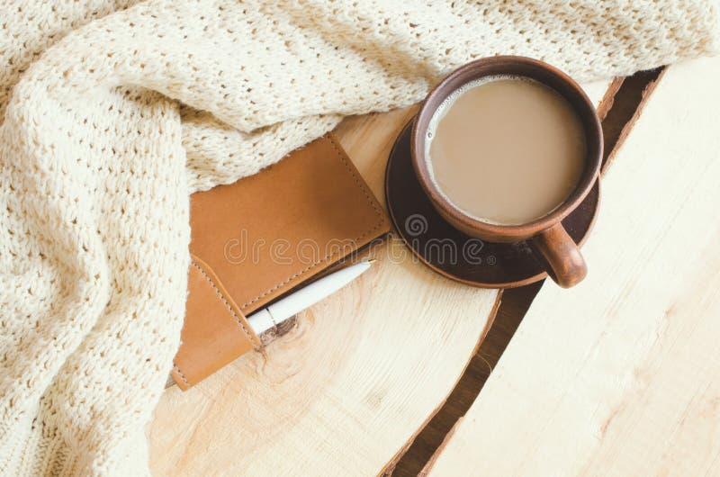 Värme hem- bakgrund för den hemtrevliga vintern, kopp av varm kakao, anteckningsbok och den stack tröjan på ljus träbakgrund fotografering för bildbyråer