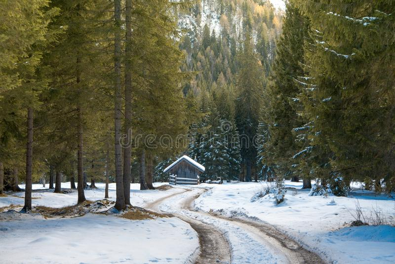 Värme vinterlandskap, den snöig vägen och det lilla huset arkivbilder