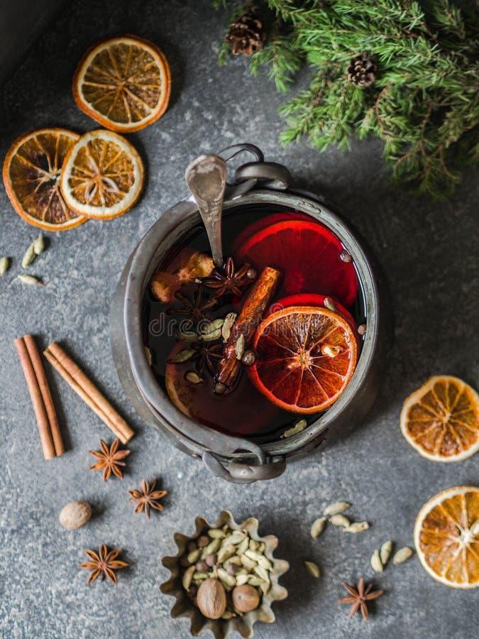 Värmealkoholdryck för traditionell vinter - funderat vin Varmt vin med frukter och kryddor i tappningmetallkastare på mörkt - grå arkivfoto