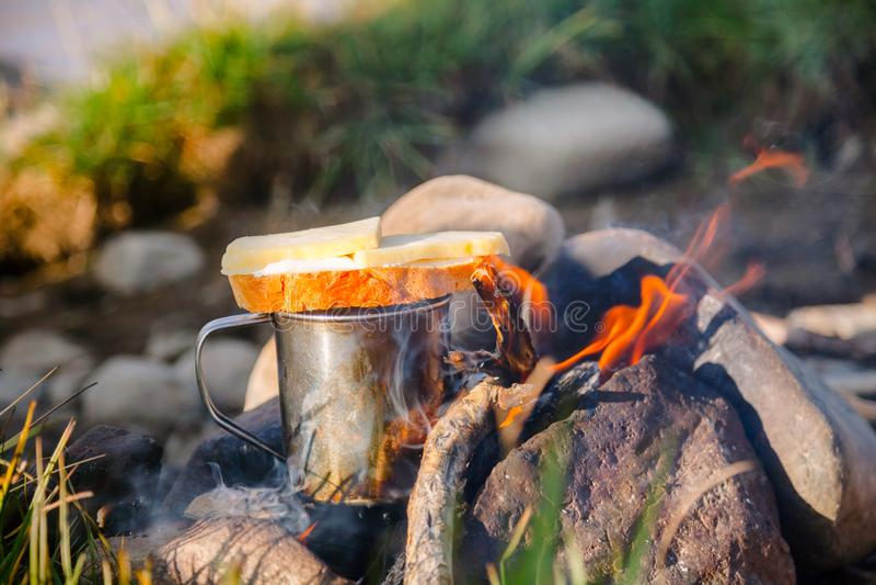Värmekopp te med smörgåsen på öppen brand på löst campa royaltyfri bild