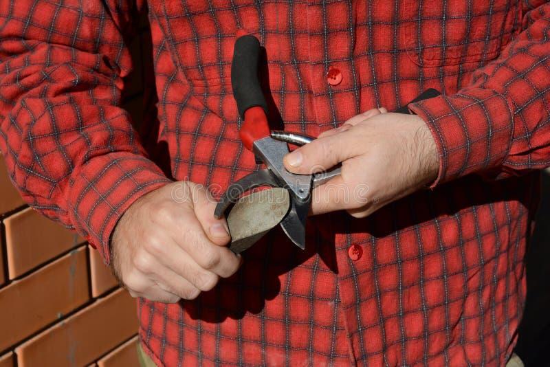 Vässa att beskära sax Trädgårdsmästare Cleaning och vässa trädgårds- hjälpmedel arkivfoto