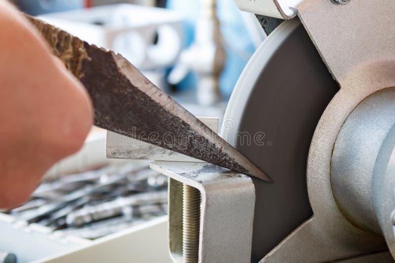 Vässa kniven av en skomakare på malande maskiner fotografering för bildbyråer