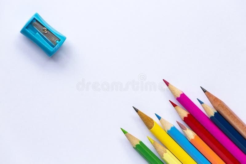 Vässare och många blyertspennor på vitbokbakgrund royaltyfri fotografi