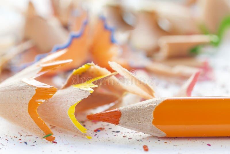 Vässat orange blyertspenna och hyvelspån arkivbild