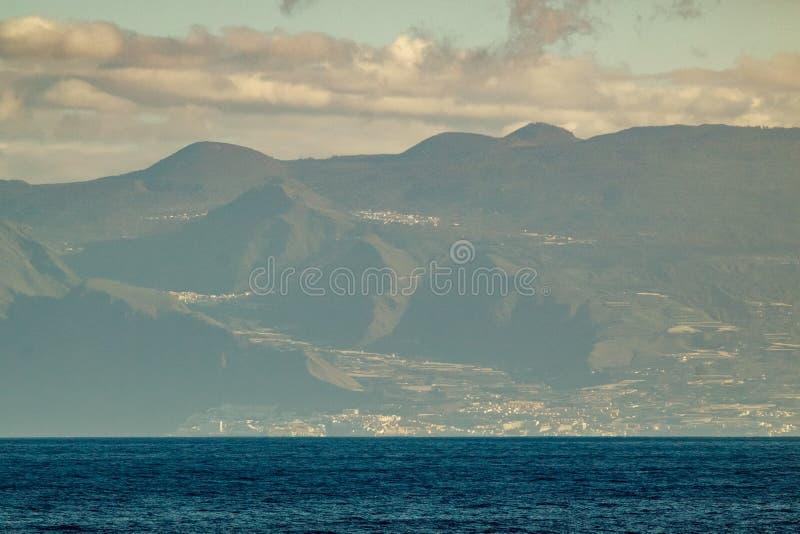 Västra del av Tenerife som ses från Gomera L?ngt linsskott Blå himmel med moln, blått vatten under rak kustlinje kanarief?gel royaltyfri bild