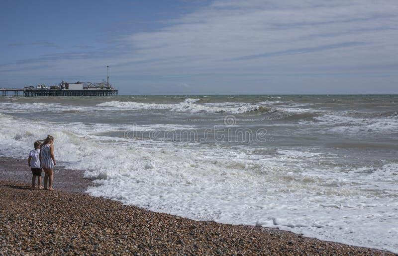 Västra pir, Brighton, England, UK - folk på stranden på en solig dag arkivfoto