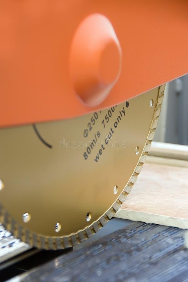 Vät såg för att klippa tegelplattan arkivfoto