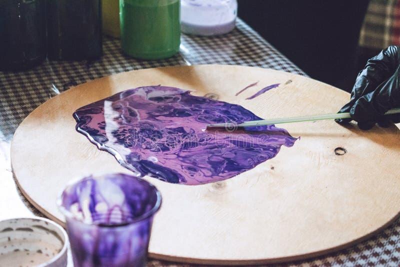 Vätskeakrylseminarium Bakgrund för parti för vätskekonstakryl Hällande akrylmålarfärg in i koppen för akryl häller målning idérik royaltyfri bild