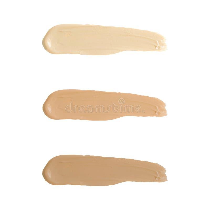 Vätskefundamentsignalfläck Ställ in kräm för täckstiftsuddskönhetsmedlet isolerad på vit bakgrund, bruntslaglängdtextur Makeup Ve arkivfoton