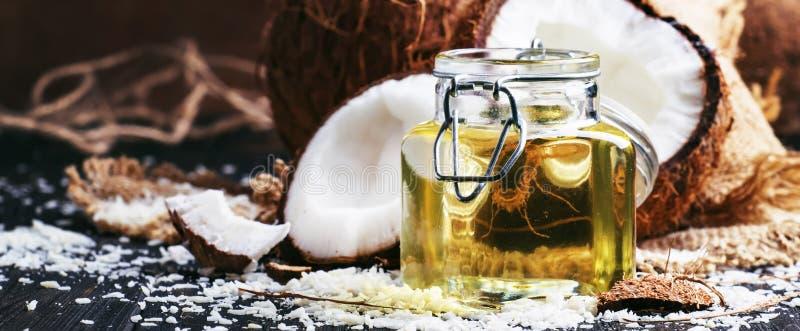 Vätskekokosnötolja i exponeringsglaskruset, brutna kokosnötter, mörk tabell, selektiv fokus arkivbilder