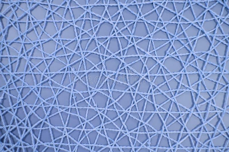 Vävt ingrepp av konstgjort material på blå bakgrund arkivfoton