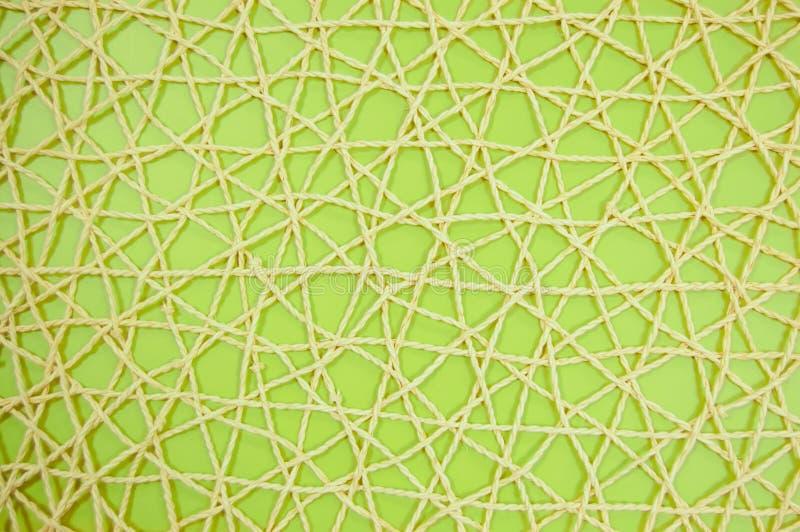 Vävt ingrepp av konstgjort material på grön bakgrund fotografering för bildbyråer