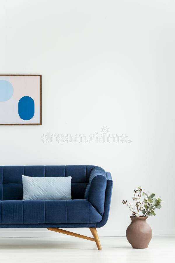 Växt bredvid den marinblåa soffan med kudden i den vita vardagsruminre med affischen Verkligt foto royaltyfria bilder