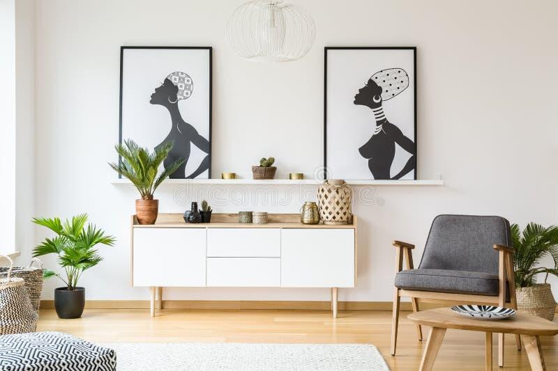 Växt bredvid det vita skåpet under affischer i ljus plan interi royaltyfri fotografi