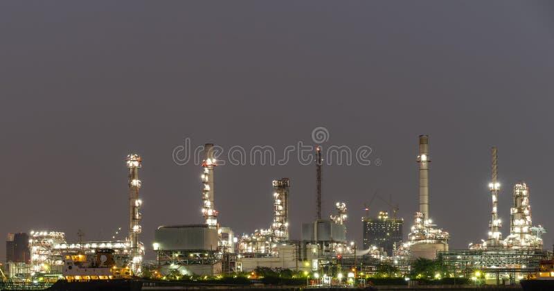 Växt för raffinaderi för nattfotoråolja och många lampglas med den petrokemiska tankfartyget eller lastfartyget på kusten av flod royaltyfria foton