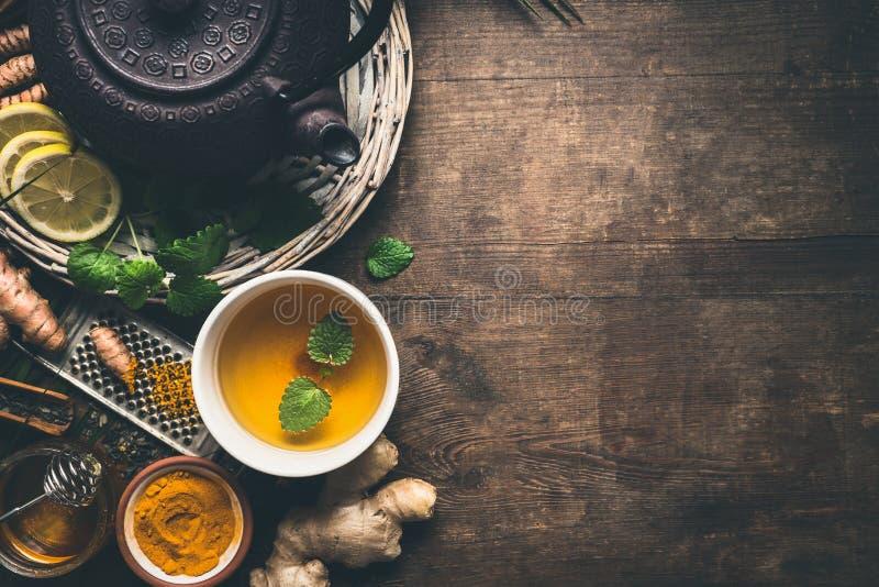 Växt- gurkmejatebakgrund Kopp av sunt gurkmejakryddate med järntekannan och ingredienser: citron ingefära, kanelbruna pinnar arkivfoton