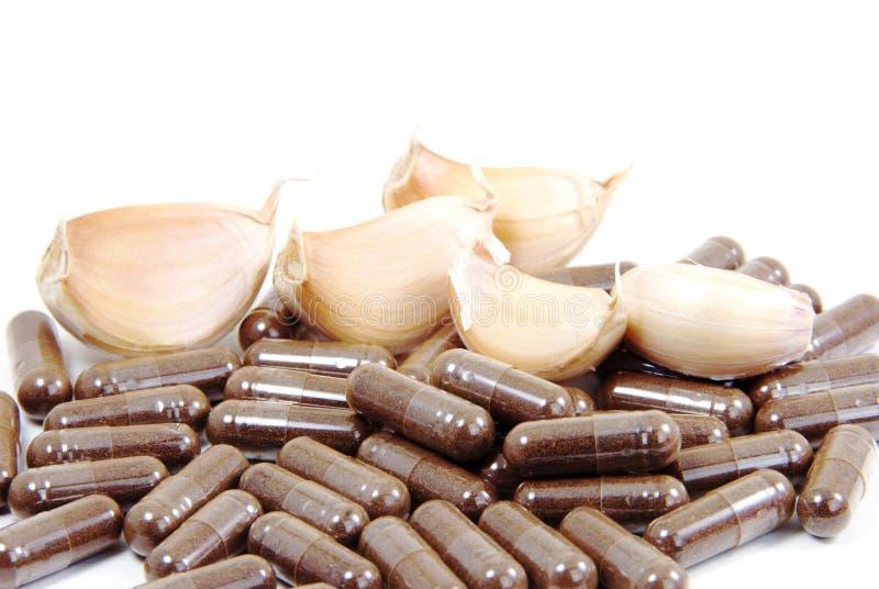 Växt- kapslar för vitlök, muntlig medicin, alternativ medicin som isoleras på vit bakgrund. arkivfoton